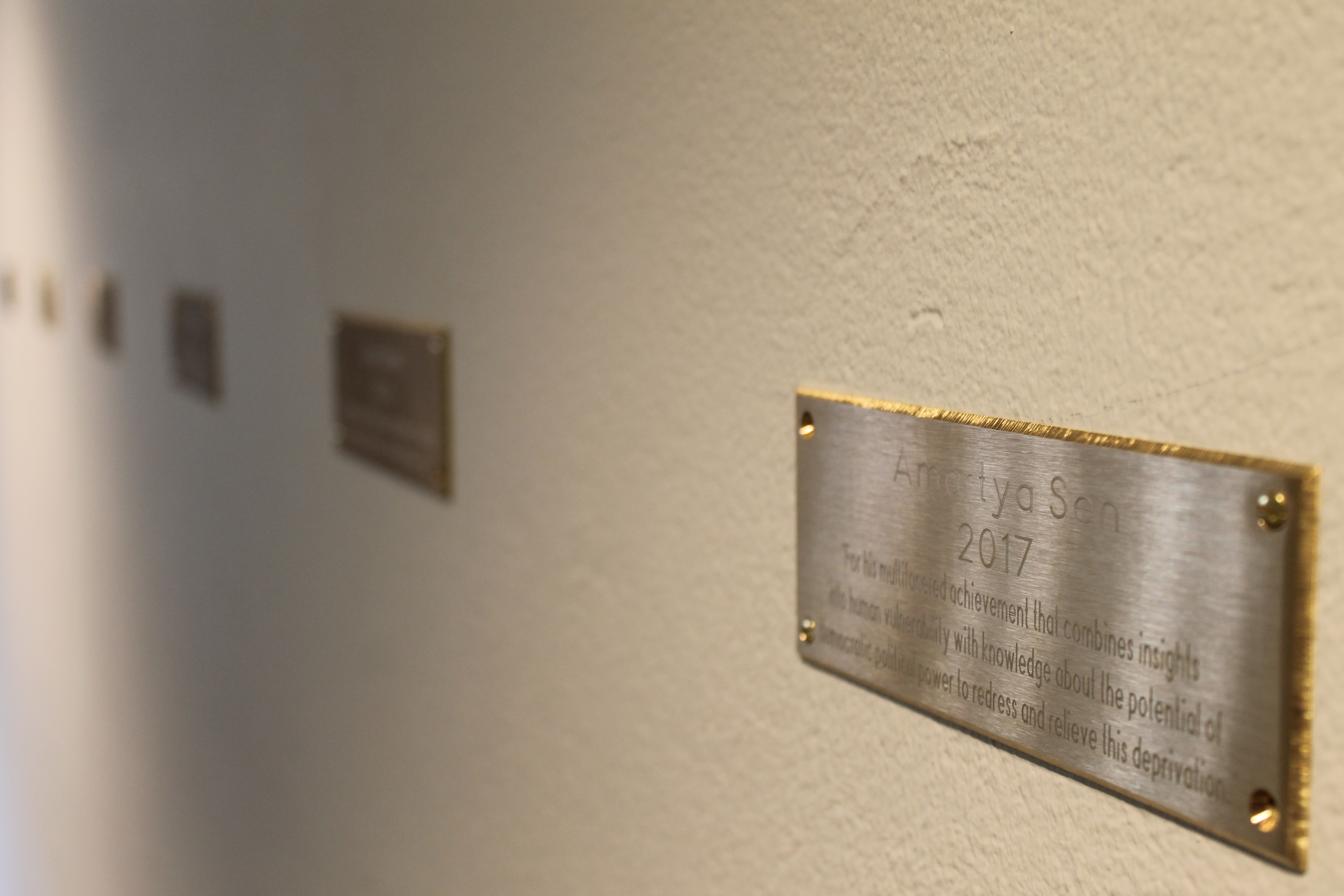 Metallic badges contain each laureate's name, year of award and award motivation.